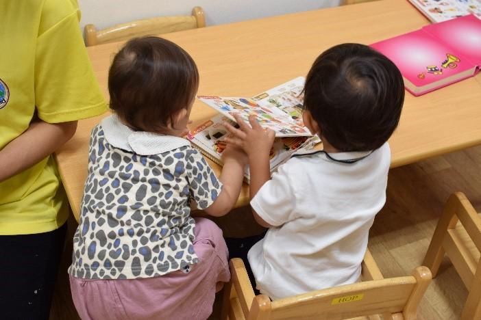 テーブルの上に座っている子供たち  中程度の精度で自動的に生成された説明